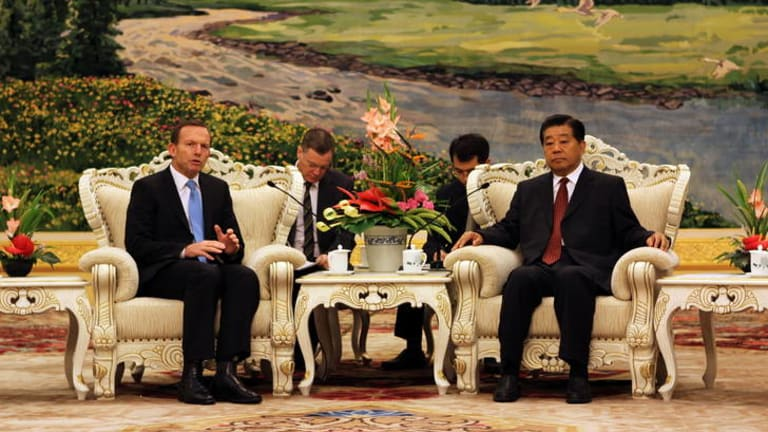 Avoiding gratuitous public advice … Tony Abbott at a meeting with Jia Qinglin, a senior member of the Chinese government.