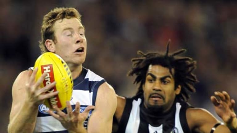 Collingwood's Harry O'Brien arrives a fraction too late to prevent Geelong's Steve Johnson from taking a mark.