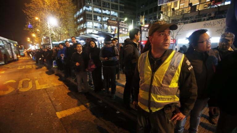 A police officer stands in the street to direct traffic as people stand in a line for public transportation after the earthquake.