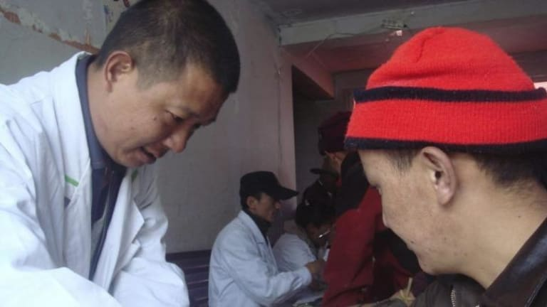 """A Chinese researcher collects a blood sample from a Tibetan man participating in the DNA study published in """"Nature"""" on Wednesday."""
