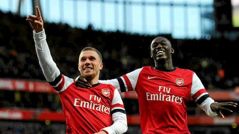 Lukas Podolski L Of Arsenal Celebrates With Team Mate Yaya Sanogo After Scoring During