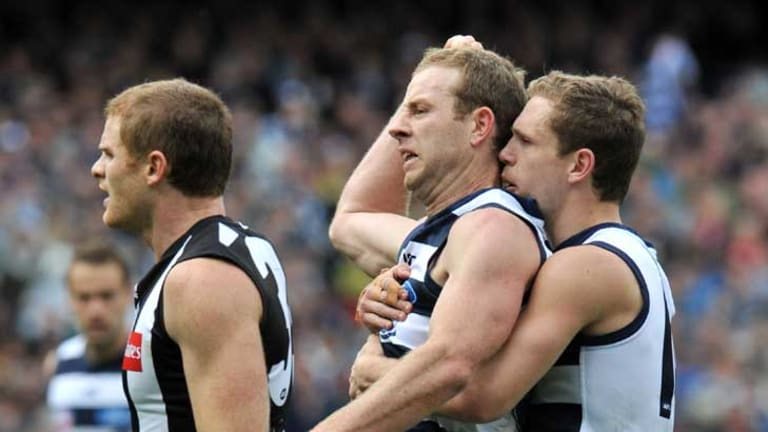 Geelong's Steve Johnson (middle) and Joel Selwood celebrate a goal.