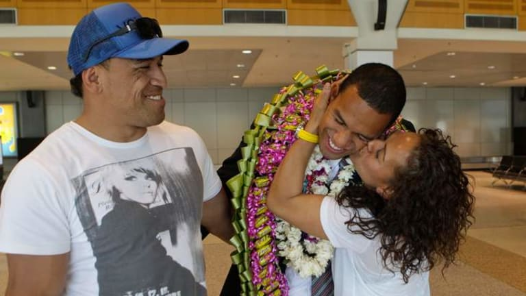Reunited: William Hopoate (centre) catches up with his parents, John and Brenda, after his two-year Mormon mission.