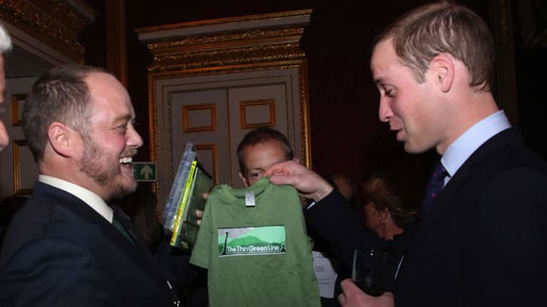 Conservationist Sean Willmore gives Prince William a T-shirt for the baby on the way.