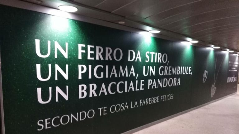 A Pandora advertisement targeting Christmas shoppers in Italy. The text says 'An iron, pyjamas, an apron, a Pandora bracelet. What do you think would make her happy?'. December 2017.?