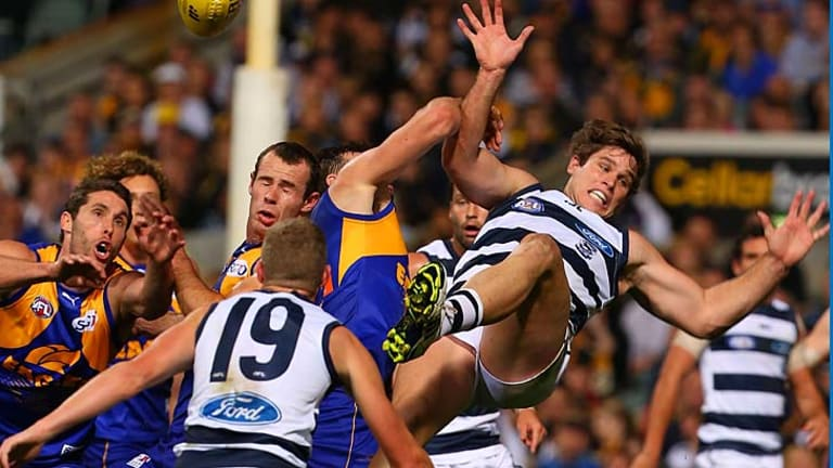 Tom Hawkins of the Cats is about to be concussed after crashing to the ground following a marking contest in the first quarter.