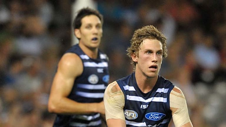 Geelong's Billie Smedts runs the ball out of the backline.