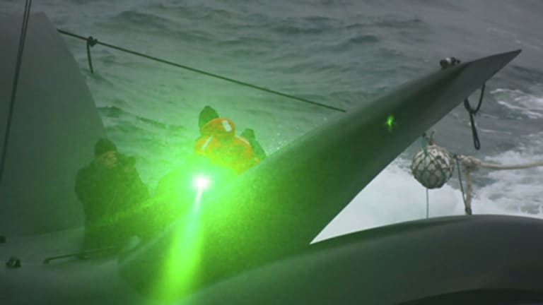A Sea Shepherd activist sends what appears to be a green laser from the deck of the anti-whaling group's  vessel, the Ady Gil, towards the Japanese whaling ship Shonan Maru No. 2.