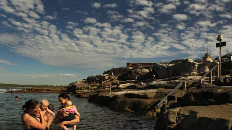 Sudden comfort … Alice Veersema, left, and her son Henry enjoy the warmer water of Mahon pool at Maroubra with Jeanine Potter and her daughter, Lani.