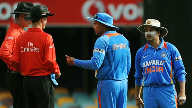 Indian captain Virender Sehwag (second from right) and Sachin Tendulkar (right), speak to umpires Paul Reiffel (left) and Billy Bowden after Ravi Aswhin ran out Lahiru Thirimanne for backing up too far.