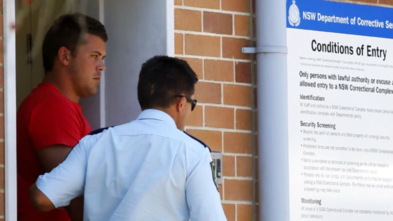 Long arm of the law ... Danny Wicks is led from Belmont police station to face court yesterday.