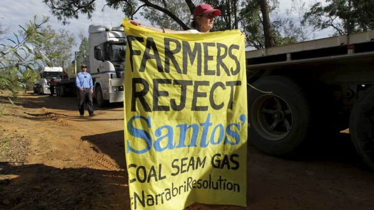 NSW farmers Ted and Julia Borowski (holding banner) protest against Santos' coal seam gas project near the Pilliga State Forest.