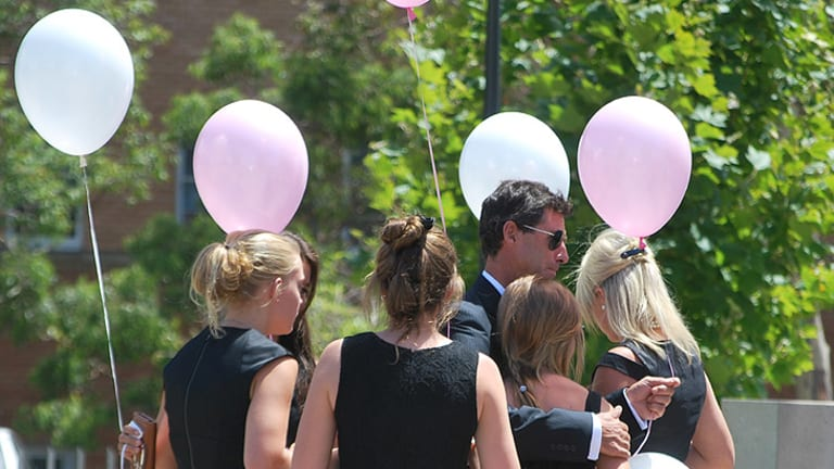 Grace Anne Cuzens is surrounded by friends and family as they prepare to release balloon at the memorial service for her younger sisters Jessica and Jane.