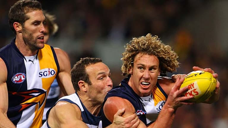 Eagle Matt Priddis looks to break a tackle by Brad Ottens of the Cats.
