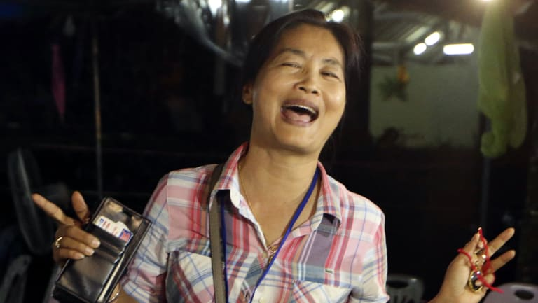 A family member smiles after hearing the news that the missing 12 boys and their soccer coach had been found, in Mae Sai, Chiang Rai province.
