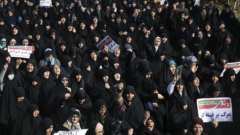 Iranian protesters chant slogans at a rally in Tehran, Iran.