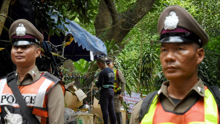 A Thai navy diver, centre, prepares his equipment at the heavily policed base camp at Tham Luang cave.