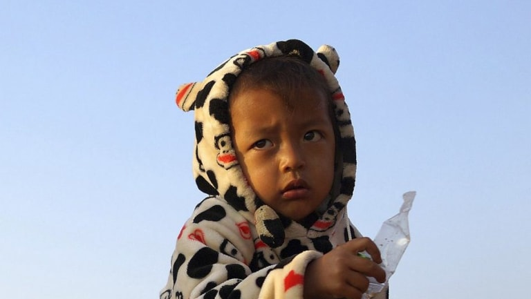 A child eats at a refugee camp at Myanmar's border town with China, in Kokang.