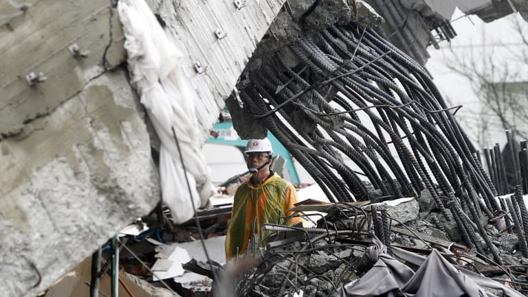 A rescuer checks damage during a search operation at a collapsed apartment building.