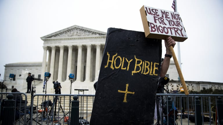 A protester dressed as the Holy Bible rallies against Masterpiece Cakeshop owner Jack Phillips outside the Supreme Court in Washington.