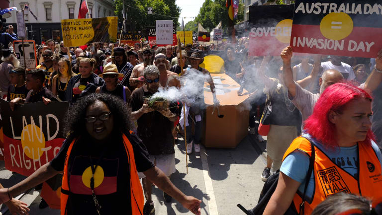 Protesters carry a coffin down Bourke Street.
