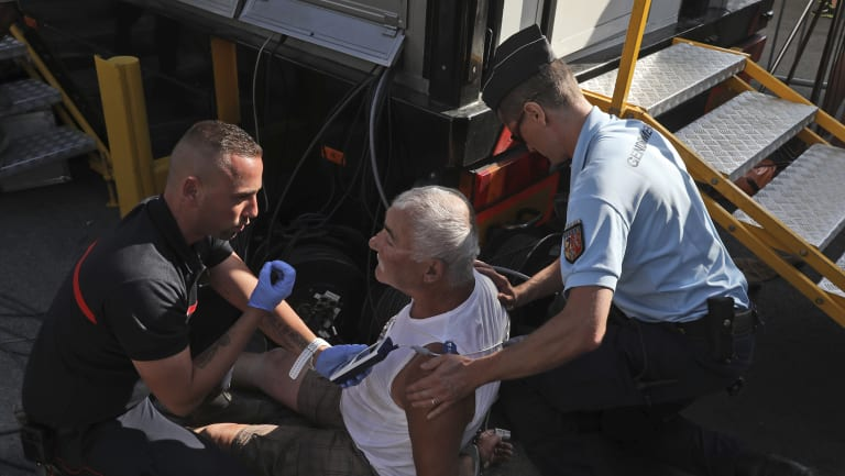 A handcuffed spectator who allegedly interfered in the race is held by police.