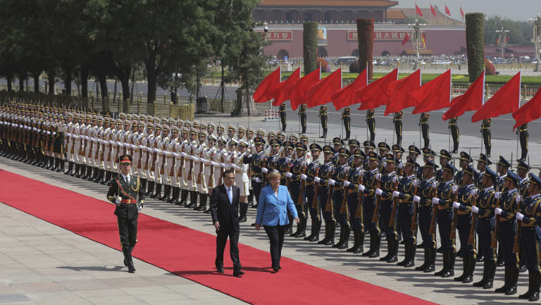 Chinese Premier Li Keqiang escorts  German Chancellor Angela Merkel past the People's Liberation Army honour guards to welcome her to China on Thursday.