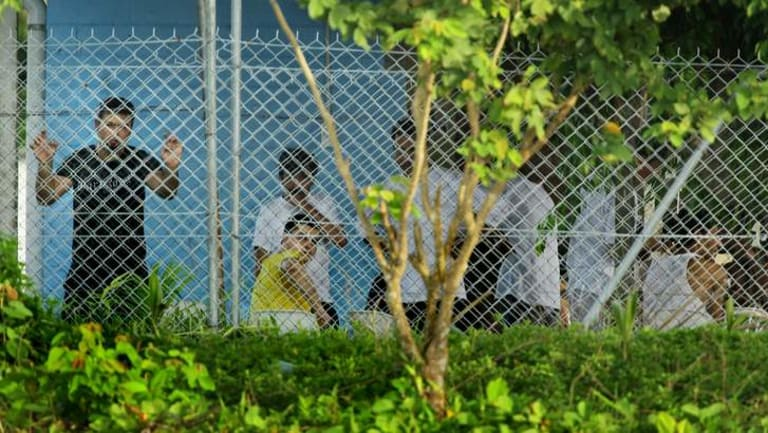 Asylum seekers stand and sit behind the wire of the Manus Island detention centre in Papua New Guinea.
