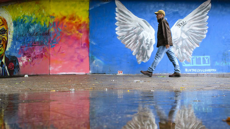 A pedestrian avoids a large puddle in Garema Place in Civic. How would you brighten up Canberra?
