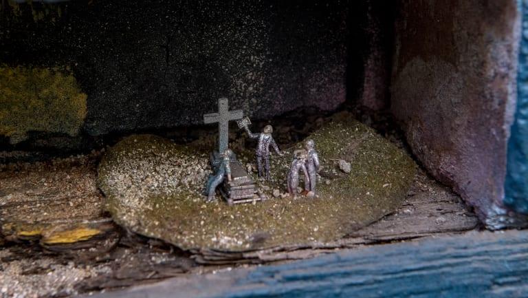 A grieving widow faints at a cemetery.