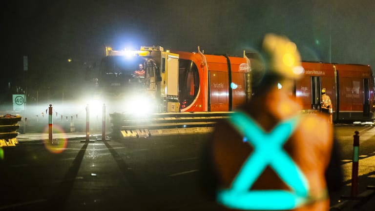A light rail vehicle is dragged on to the tracks on Flemington Road for testing on Monday night