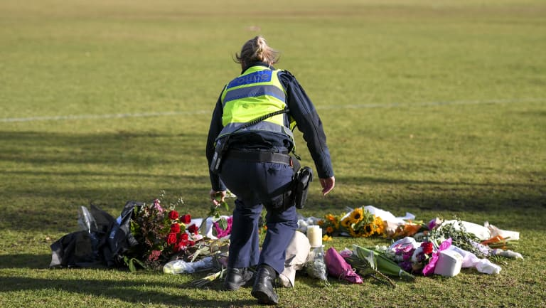 A female police officer lays flowers at the scene where Eurydice Dixon\'s body was found. 15 June 2018. The Age News. Photo: Eddie Jim.