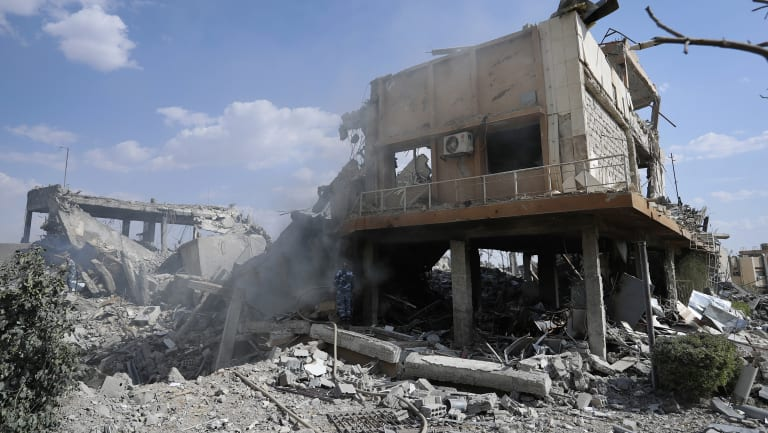 A fireman extinguishes smoke that rises from the damage of the Syrian Scientific Research Center.