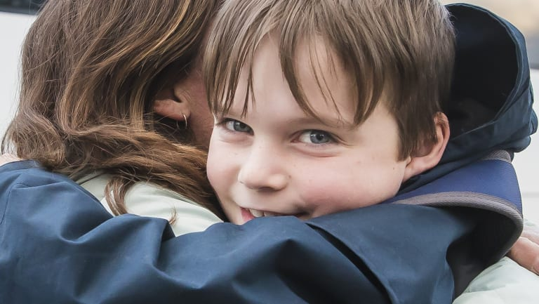 Timothy Pengilly hugs his mother Roz after getting off the school bus near his Murrumbateman home. He makes the long commute to Canberra every school day.