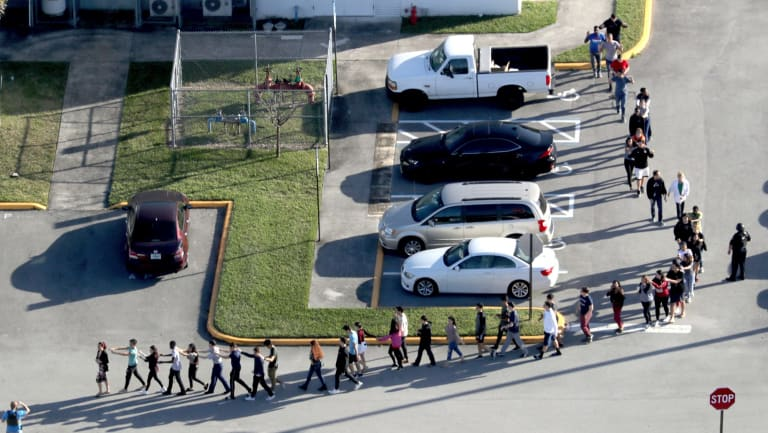 Students are evacuated by police from Marjory Stoneman Douglas High School.