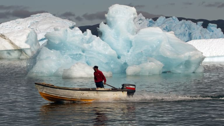 A fisherman sails past melting icebergs in Greenland,