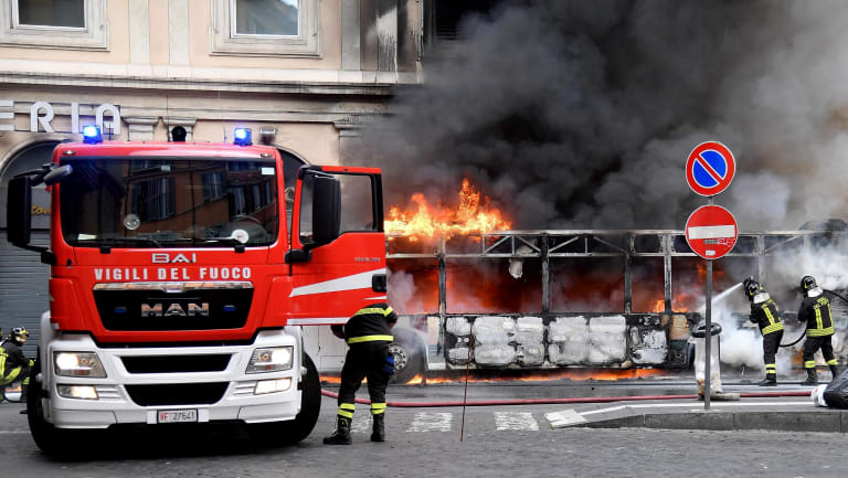 Firefighters hose down a fire on a bus in central Rome.