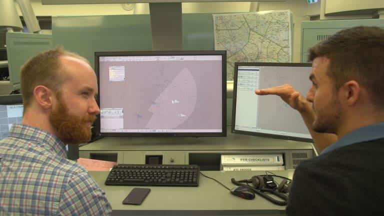Liam Mannix gets a briefing from air traffic control specialist Sean Menere.