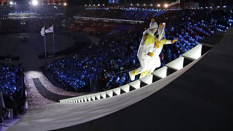 North Korea's Jong Su Hyon and South Korea's Park Jong-ah carry the torch during the Winter Olympics opening ceremony.