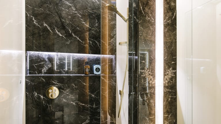 The facility has terrazzo floors, wood paneled walls and black marble showers.