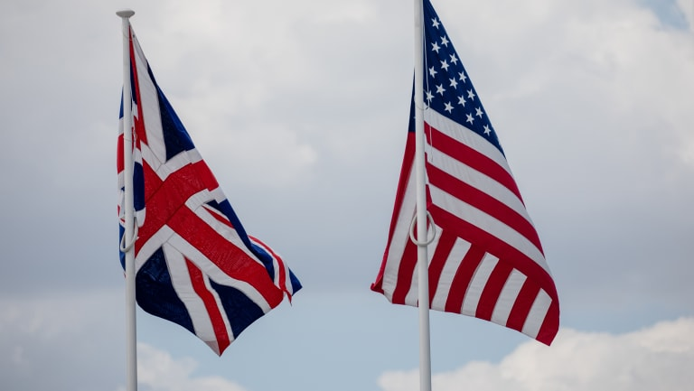 A British Union flag, also known as the Union Jack, left, flies beside a US flag.