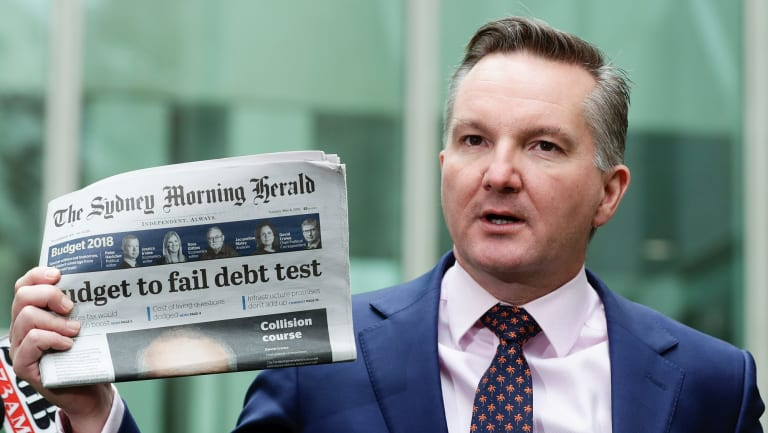 Shadow Treasurer Chris Bowen holds a copy of today's Sydney Morning Herald as he addresses the media ahead of budget night.