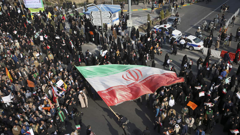 A demonstrator waves a huge Iranian flag during a pro-government rally in the northeastern city of Mashhad, Iran.