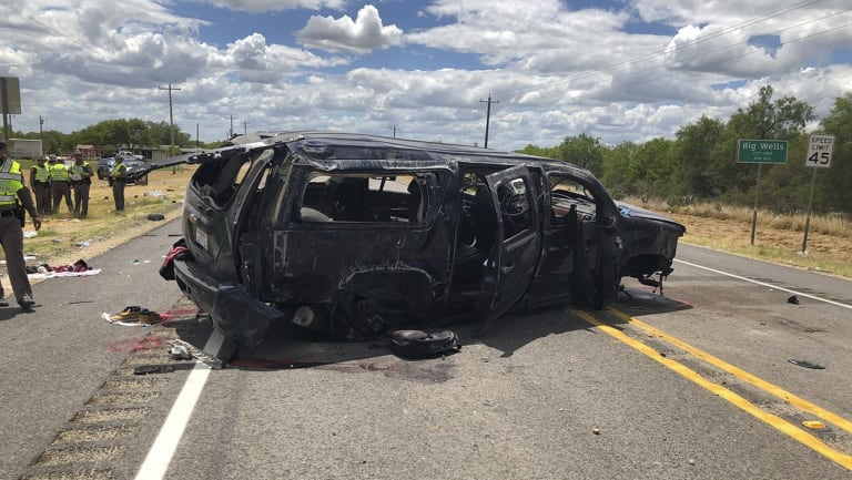 A heavily damaged SUV is seen on Texas Highway 85 in Big Wells, Texas, after crashing while carrying more than a dozen people fleeing from Border Patrol agents.