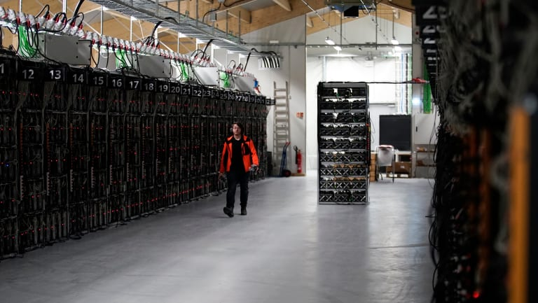 A worker walks along a row of computer rigs that run around the clock 'mining' bitcoin inside the Genesis Mining cryptocurrency mine in Keflavik, Iceland.