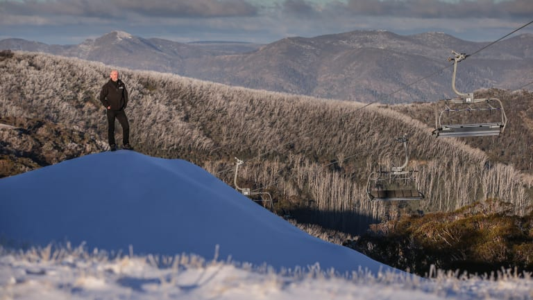Mark Bennetts, CEO of Mt Buller and Mt Stirling Resorts, stands on a huge pile of man made snow.
