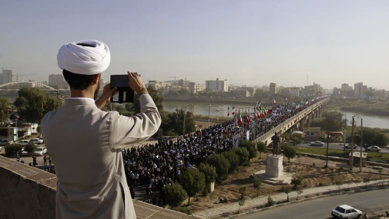 In this photo provided by the Iranian Students' News Agency, a clergyman takes a picture of a pro-government demonstration in the southwestern city of Ahvaz, Iran.</p> <p>