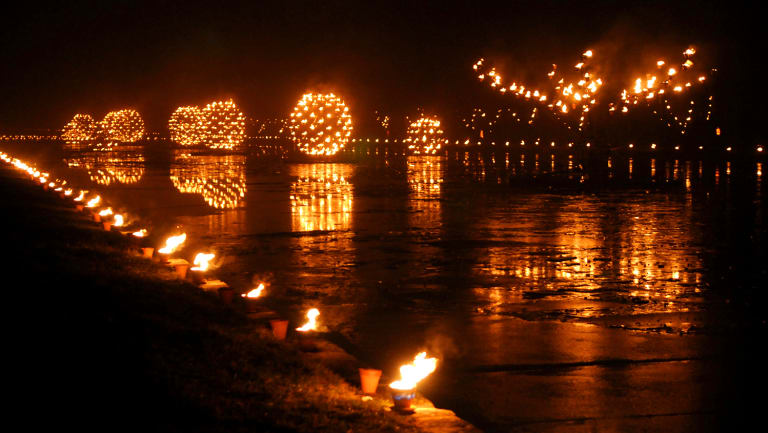 Thousands of carefully controlled flames reflect off the water.