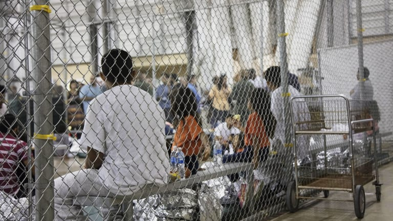 People taken into custody related to cases of illegal entry into the United States, sit in one of the cages at a facility in McAllen, Texas.