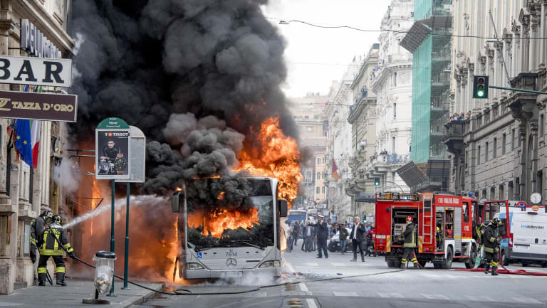 Firefighters spray water as they try to extinguish a fire on a public transportation bus in central Rome this week.